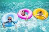 picture of floaties  - Group of cute kids playing on inflatable tubes in a swimming pool on a sunny day - JPG