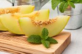 image of honeydew melon  - Juicy honeydew melon on a wooden table background - JPG