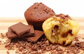 picture of chocolate muffin  - Delicious fresh baked muffins grated chocolate and portion of chocolate lying on wooden cutting board - JPG