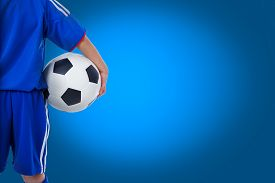 picture of balls  - Back view of youth soccer player in blue uniform and little kid holding a ball - JPG
