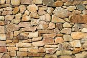 stock photo of wall-stone  - An old brown colors stone wall background - JPG
