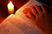 Bible by candle light with hands resting