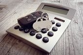 Car shape keyring and key on calculator concept for motoring costs, finance, insurance, servicing or poster