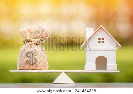poster of Home And Money Bag Put On The Scales With Balance Put On The Wood In The Public Park, Saving For Buy