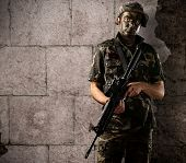 portrait of young soldier with jungle camouflage holding a rifle against a grunge bricks wall