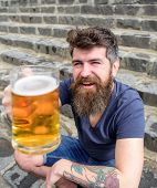 Hipster On Cheerful Face Drinks Beer Outdoor. Celebration Concept. Man With Beard And Mustache Holds poster