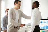 Caucasian Team Leader Or Company Boss Promoting Successful African Manager Handshaking Expressing Gr poster