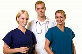 stock photo of medical assistant  - Two woman healthcare workers with one male in the middle wearing a doctors lab coat - JPG
