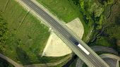Aerial Top View of White Truck with Cargo Semi Trailer Moving on Road in Direction f Loading Warehou poster