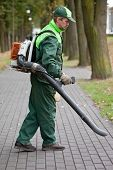 stock photo of leaf-blower  - Landscaper cleaning the runway in park by petrol leaf blower - JPG