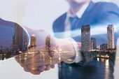 Double Exposure Concept. Investor Business Handshake With City Night. Businessman Shaking Hands Usin poster