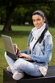 Attractive woman with laptop and sandwich sitting in park, looking at camera