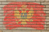 Flag Of Montenegro On Grunge Brick Wall Painted With Chalk
