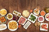 An Overhead Photo Of An Assortment Of Spanish Tapas Food, Shot From The Top On A Dark Rustic Backgro poster