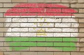 Flag Of Tajikistan On Grunge Brick Wall Painted With Chalk