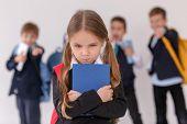 Children bullying their classmate on light background poster