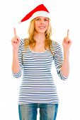 Pretty Teen Girl In Santa Hat Pointing Up