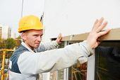 Plaster facade builder worker with roller at thermal insulation works