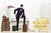 Macho Elegant On Thoughtful Face Standing Near Pile Of Vintage Suitcase. Man, Traveller With Beard A poster