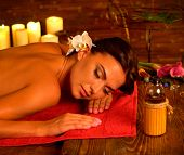 Massage of woman in spa salon. Girl on candles background in massage spa room. Luxary interior in or poster