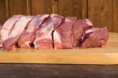 Raw Fat Cuting Pieces Of Pork On Wooden Background. Piece Of Fresh Boneless Pork, Neck Part Or Colla poster