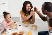 Wife And Husband Feeding Each Other While Having Breakfast With Kids poster