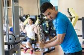 Side view of a young man exhaling while exercising triceps pushdown at the rope cable machine during poster