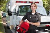 Portrait of a happy paramedica carrying a portable oxygen unit