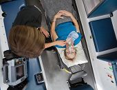 pic of triage  - Overhead view of senior woman patient in ambulance receiving oxygen and having heart rate measured - JPG