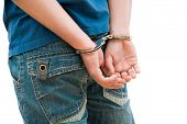 stock photo of handcuffs  - Young man in handcuffs in rear view - JPG