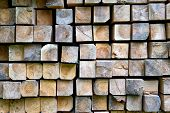 Stack Of Wooden Bars In Warehouse. Stacked Wooden Beams Of Square Section. poster