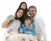 stock photo of indian sari  - Happy Indian family with two children in traditional costume sitting on white background - JPG