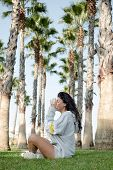The Girl Sitting On The Green Grass Among Many Palm Trees Meditates And Relaxes poster