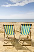 Two Deck Chairs On The Beach