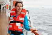 Beautiful woman wearing in orange life jacket looks into distance at deck of ship