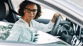 Young Female Entrepreneur Driving A Car Looking Away poster