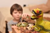 Dinosaur Toy. Boy Having Fun Playing With A Toy Dinosaur, Selective Focus poster