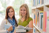 Two female students at school library studying books together