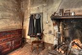 Old Times Farmhouse - Interior Of An Old Country House With Fireplace, Kitchen Cupboard, Ancient Man poster