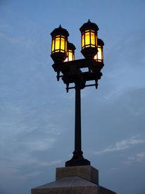 stock photo of lamp post  - Four Yellow Lamp Streetlight against blue sky  - JPG