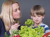 Kleiner Junge mit seiner Mutter, die sich weigern, grünen Salat essen