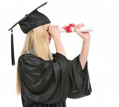 Young Woman In Graduation Gown Looking Into Distance Through Dip
