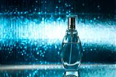 Perfume on blue shiny background