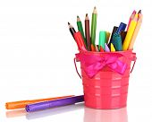 Colorful pencils and felt-tip pens in pink pail isolated on white