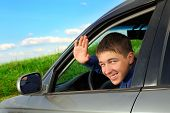 stock photo of goodbye  - happy young man sitting in the car and wave goodbye - JPG