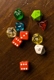 stock photo of dodecahedron  - Multicolored role play dice sitting on a wooden table top - JPG
