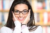 Portrait Of Beautiful Young Woman Wearing Glasses, Bookshelf On Background