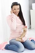image of toy phone  - Smiling young woman sitting between heels on floor at home - JPG