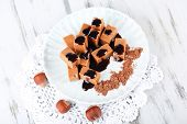 Many toffee on plate on napkin on wooden table