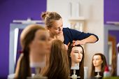 Pretty female hairdresser/haidressing apprentice/student training on an apprentice head